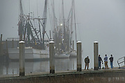 Shrimper wait for the fog to lift before heading out on Shem Creek during a foggy winter morning in Charleston, South Carolina.