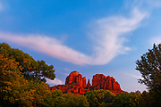 A band of clouds, showing a hint of pink at dusk, passes over Cathedral Rock near Sedona, Arizona. Cathedral Rock is a 4,967 foot (1,514 meter) sandstone butte that is located in the Coconino National Forest.