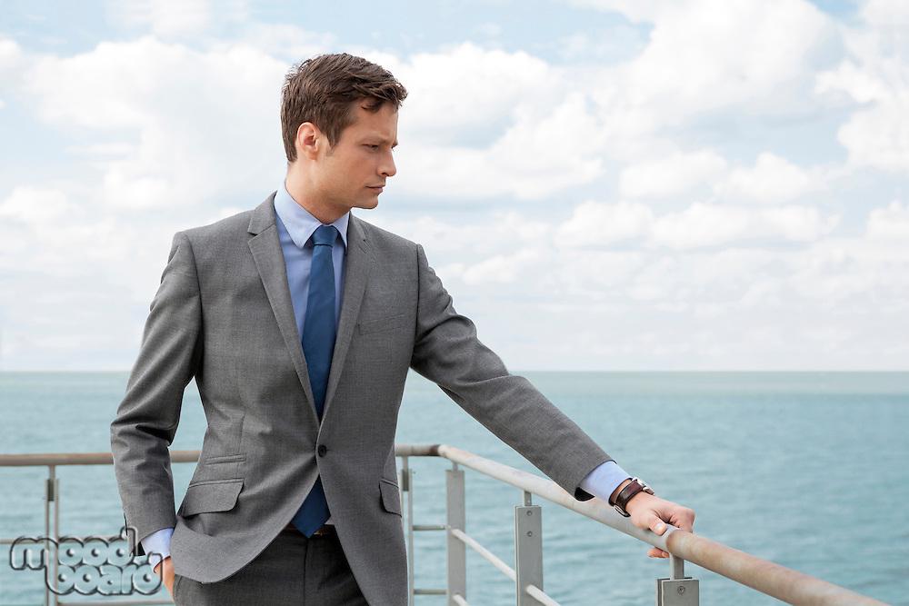 Worried businessman standing by terrace railings