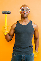 Portrait of a Mid 30's African American man holding a sledge hammer, wearing protective goggles, and gloves...Model release: 20060425_066_MR_A