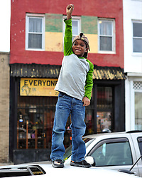 A little boy stands on top of a car holding his hand high in celebration after officers were charged in the death of Freddie Gray on May 1, 2015, in Baltimore, Md.
