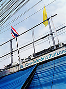 Thai and Royal flags with phone and electric wires.