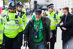 London, UK. 9 October, 2019. David, a great grandfather, is arrested by police officers using Section 14 of the Public Order Act 1986 after blocking Whitehall on the third day of Extinction Rebellion International Rebellion protests to demand a government declaration of a climate and ecological emergency, a commitment to halting biodiversity loss and net zero carbon emissions by 2025 and for the government to create and be led by the decisions of a Citizens' Assembly on climate and ecological justice.