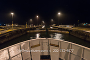 The gatun locks in the Panama canal are opened for a ship to transit the Panama Canal at nighttime.