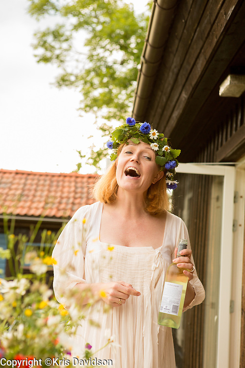 Woman wearing a Midsommar wreath and holding wine on Öland, a Swedish island in the Baltic Sea. The longest day of the year is a beloved holiday in Sweden; the cities are empty as the locals take to the countryside for a day of dancing and singing with family and friends.