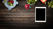 Red and green fruits, vegetables and herbs on wood background with customizable black screen device. Top view with copy space.