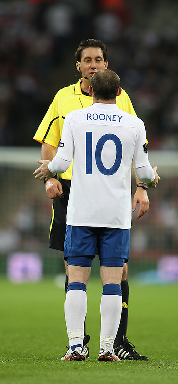 12/10/2010 International football. England v Montenegro.<br /> Wayne Rooney looks up at tall German referee Manuel Grafe.<br /> Photo: Mark Leech.