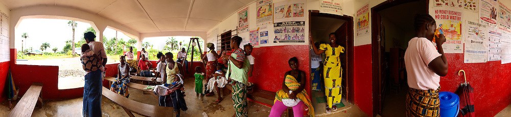 Kingsville clinic is supported by Save the Children. In the dooway is Kaytor, the midwife, Kingsville #7, Liberia.