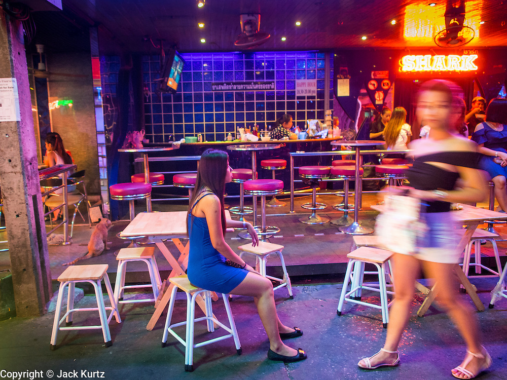 "22 MAY 2014 - BANGKOK, THAILAND: Workers at a bar on Soi Cowboy, one of Bangkok's ""adult entertainment"" districts, have no customers after the army announced an overnight curfew. The Thai army suspended civilian rule, suspended the constitution and declared the ""military takeover of the nation."" The announcement came just before evening as a meeting between civilian politicians and the army was breaking up with no progress towards resolving the country's political impasse. Civilian politicians were arrested when the meeting ended. The army also declared a curfew from 10PM until 5AM.    PHOTO BY JACK KURTZ"