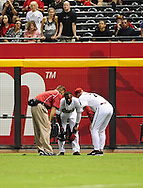 Sep. 27 2011; Phoenix, AZ, USA; Arizona Diamondbacks manager Kirk Gibson (right) and trainer talk with outfielder Justin Upton (10) after being hit in the face attempting to catch a fly ball during the tenth inning against the Los Angeles Dodgers at Chase Field. The Diamondbacks defeated the Dodgers 7-6 in extra innings.  Mandatory Credit: Jennifer Stewart-US PRESSWIRE