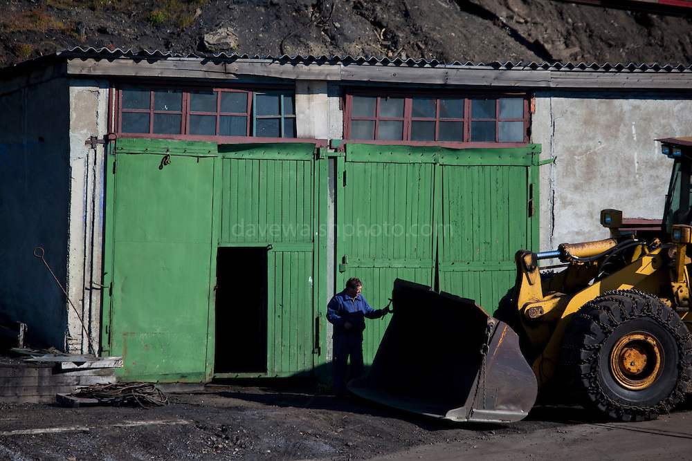 Man working on earthmover, Barentsburg, a Russian coal mining town in the Norwegian Archipelego of Svalbard. Once home to about 2000 miners and their families, less than 500 people now live here.