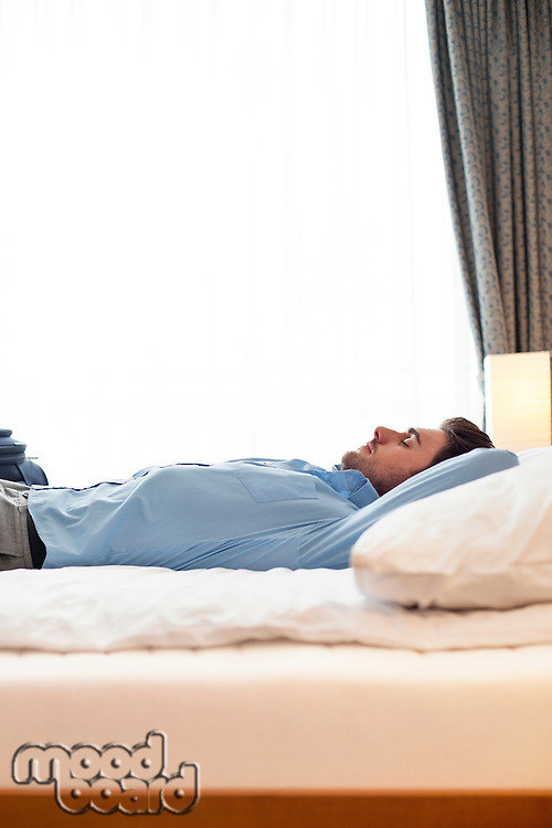 Side view of young businessman sleeping on bed in hotel room