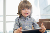Portrait of cute boy holding tablet computer at home