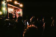 Ravers dancing near neon karaoke sign and pirate flag, BulgariaTek, Bulgaria, August 2011