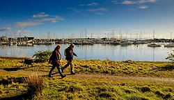 A man and a woman walk a dog at the marina at Pwllheli, North Wales, UK<br /> <br /> (c) Andrew Wilson | Edinburgh Elite media