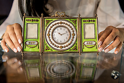"© Licensed to London News Pictures. 31/05/2019. LONDON, UK. A staff member presents ""A rare Fabergé silver-gilt enamel and seed pearl triptych clock and frame"" by workmaster Johan Victor Aarne, 1880-1904 (Est. GBP 150,000-200,000) at a preview of works from the upcoming sale of Russian Pictures, Works of Art, Fabergé & Icons Sales at Sotheby's, New Bond Street, on 4 June 2019.  Photo credit: Stephen Chung/LNP"