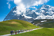Japanese tourists on walking trail by the North Face of the Eiger mountain in the Swiss Alps, Bernese Oberland, Switzerland