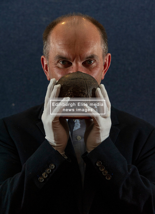 Pictured: Phil Gregory of Lyon and Turnbull holds on carefully to the unsusual coconut collection box<br /> <br /> A coconut collecting box valued at GBP500-GBP700, once in the possession of Scottish missionary John Paton, is among the highlights of the African & Oceanic sale which takes place on 1 May.<br /> <br /> Ger Harley | EEm 29 April 2019