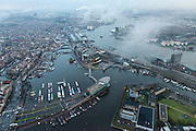 Nederland, Noord-Holland, Amsterdam, 16-01-2014;<br /> Overzicht Amsterdam rond het Centraal station (m) met nieuwe overkapping, onder in beeld NEMO en Oosterdok met Openbare Bibliotheek en Conservatorium, links het oude centrum, rechts Muziekgebouw en Bimhuis, en Piet Heinkade, Amsterdam Noord met EYE, de wijk Overhoeks, achter in beeld het Westelijk Havengebied met de schoorsteenpijpen van de vuilverbranding.<br /> Overview Amsterdam around the Central station (m), Oosterdoks with Public Library, and Conservatory(m, l), left the old town, right Music Building and Bimhuis, Piet HeinKade, Amsterdam North and EYE, the Overhoeks district, on the horizon the Western harbor area with chimney pipes of the waste incineration.<br /> luchtfoto (toeslag op standard tarieven);<br /> aerial photo (additional fee required);<br /> copyright foto/photo Siebe Swart