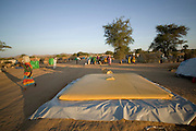 The arrival of an Oxfam water truck to the Breidjing Refugee Camp is an instant call for everyone in the camp to show up with a container. The trucks fill yellow waterbed-like bladders, which rest on low platforms. The water flows through buried pipes to watering centers, where half a dozen people can fill up at once without wasting any precious liquid. Hungry Planet: What the World Eats (p. 60). /// This image is featured alongside the Aboubakar family images in Hungry Planet: What the World Eats. (Please refer to Hungry Planet book p. 56-57 for a family portrait.)