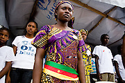 A young woman wearing a belt in the national colors of Cameroon stands during a ceremony held on the occasion of the visit of UNICEF Goodwill Ambassador Mia Farrow in the town of Mandjou, Cameroon on Wednesday September 16, 2009..