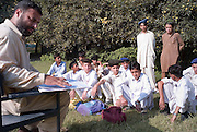 Young boys sit on open grass whilst a teacher checks the register in the grounds of their destroyed Nazarabad Government Boys School in SWAT...Some pupils have returned to the makeshift open-air class rooms whilst others still fear the return of the Taliban and choose to stay away from lessons. .