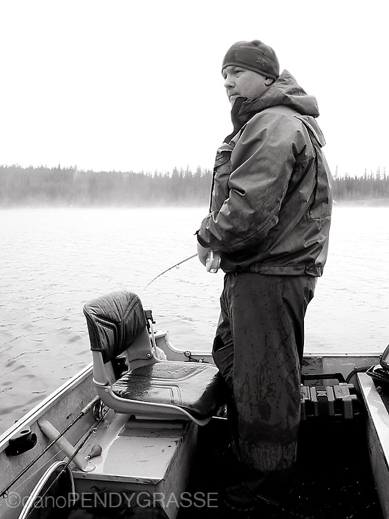 A black and white photo of a fisherman on a misty early morning lake in BC, Canada.