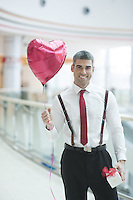 Businessman holding heart shaped balloon and present