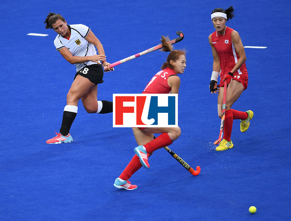 Germany's Julia Muller (L) hits past South Korea's Park Seunga (C) and South Korea's Kim Jongeun during the women's field hockey Germany vs South Korea match of the Rio 2016 Olympics Games at the Olympic Hockey Centre in Rio de Janeiro on August, 10 2016. / AFP / MANAN VATSYAYANA        (Photo credit should read MANAN VATSYAYANA/AFP/Getty Images)