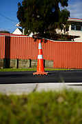 a single traffic cone sits in the middle of the road beside the new tarmac freshly laid by road workers at Browns Bay, Auckland, New Zealand