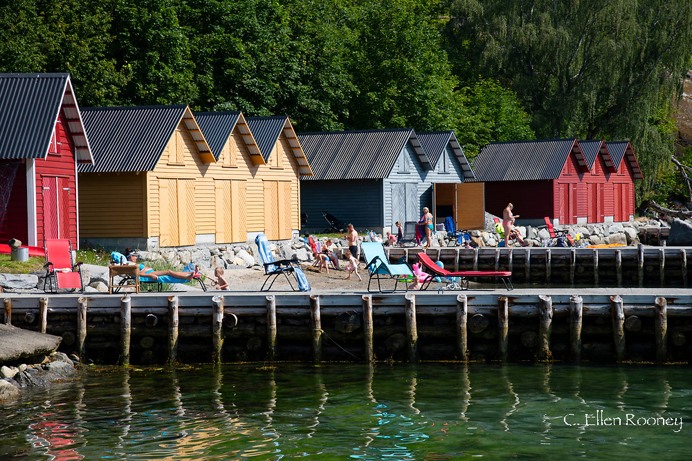 Sun bathers in front of colourful timber dock houses on the waterfront in Solvorn on Lustra Fjord, Vestlandet, Norway, Europe