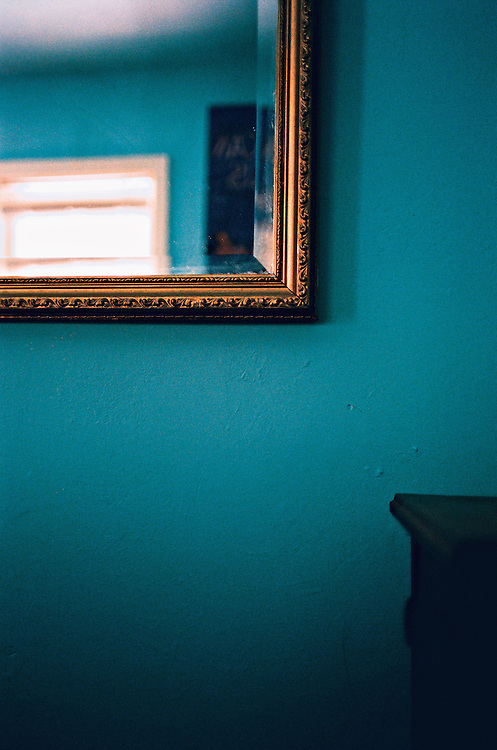 Mirror, blue wall and nightstand