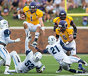 The University of Mary Hardin-Baylor's Zach Anderson (1) leaps over Kean's Corey Miller (52) and Darren Dixon (21) during game action at Crusader Stadium in Belton on Saturday, Sept. 27, 2014.
