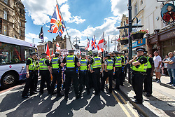 """© Licensed to London News Pictures . 07/07/2018 . Leeds , UK . Police contain the march on Boar Lane . An anti-Islam demonstration by supporters of jailed EDL founder Tommy Robinson , including those from the """" Yorkshire Patriots """" and """" First for Britain """" , in Leeds City Centre , opposed by anti-fascists . Robinson ( real name Stephen Yaxley-Lennon ) was convicted of Contempt of Court in May 2018 after committing a second offence , whilst serving a suspended sentence for the same crime . Photo credit : Joel Goodman/LNP"""