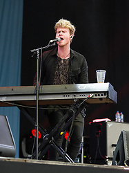 © Licensed to London News Pictures. 12/06/2015. Newport, UK.   Kodaline performing live at Isle of Wight Festival 2015, Day 2 Friday.  In this picture - Steve Garrigan.  This afternoon has seen torrential downpours of rain after the last day of hot sunshine.   Photo credit : Richard Isaac/LNP