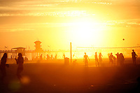 21 June 2008:  Record Summer heat brought  thousands of people to the beach in Southern California the first weekend of summer. Sunset with volleyball players and the pier at tower 9 in Huntington Beach, CA.