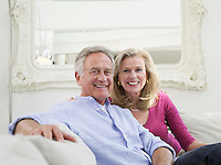 Relaxed portrait of successful mature couple in white home interior