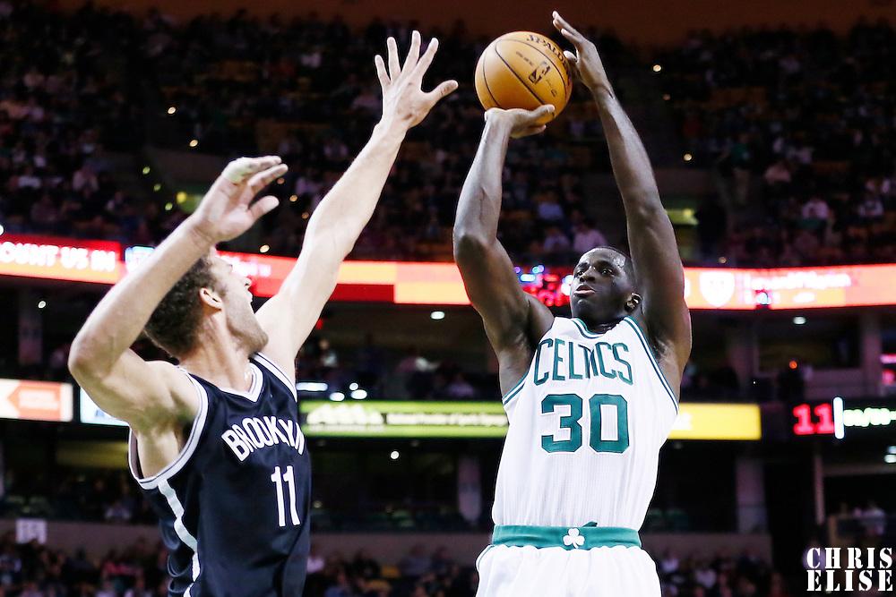 28 November 2012: Boston Celtics power forward Brandon Bass (30) takes a jumpshot over Brooklyn Nets center Brook Lopez (11) during the Brooklyn Nets 95-83 victory over the Boston Celtics at the TD Garden, Boston, Massachusetts, USA.