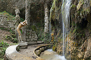 Ragazza che si Asciuga, or Girl drying her hair, sculpture by Venanzo Crocetti, by the waterfall in the gardens of Vittoriale degli italiani, or The Shrine of Italian Victories, the home, estate and museums of Gabriele D'Annunzio, 1863-1938, Italian writer, soldier and fascist, at Gardone Riviera, Lake Garda, Brescia, Lombardy, Italy. The estate consists of the Prioria, where d'Annunzio lived 1922-38, an amphitheatre, the protected cruiser Puglia, the MAS vessel used by D'Annunzio in 1918 and a mausoleum. It is part of the Grandi Giardini Italiani. Picture by Manuel Cohen