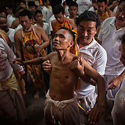 Devotees to the Chinese shrine of Kathu gather prior to fire walking ceremonies at the annual Vegetarian Festival in Phuket, Thailand, Sunday,  Oct. 13, 2013. The a traditional Chinese vegetarian festival  emphasizes merit making and ritual cleansing of the body to mark the nine-day-long festival.  It also features face-piercing, spirit mediums, and strict vegetarianism.