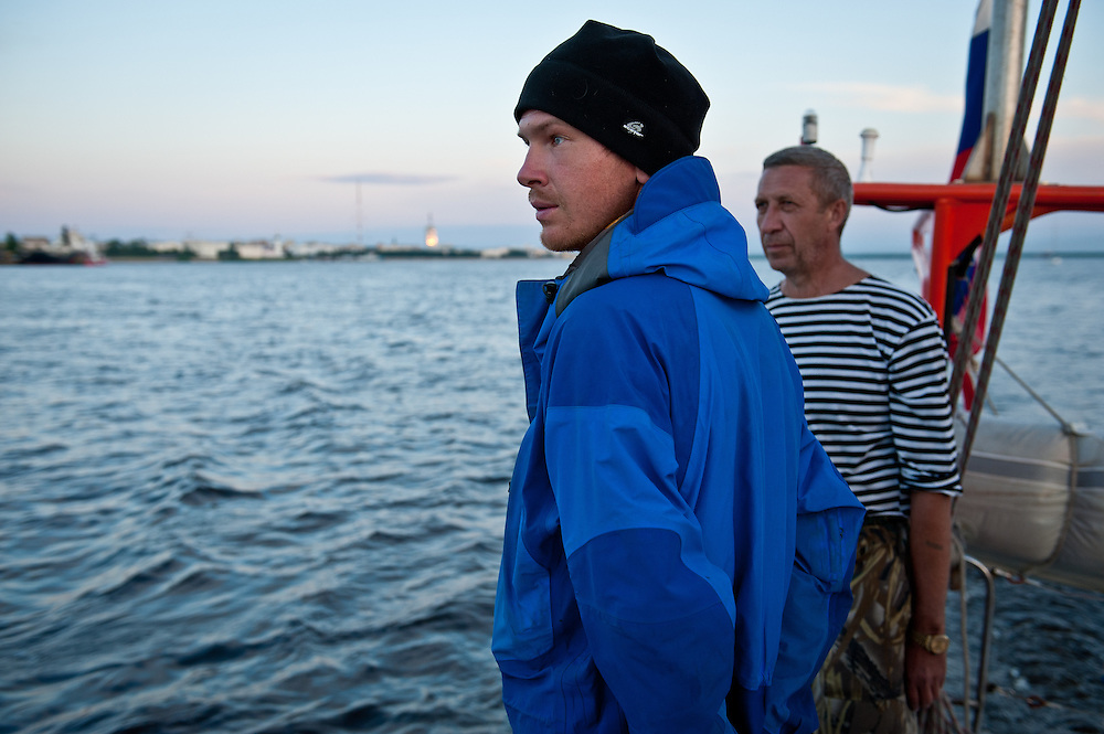 Crew members on Peter 1 watch the sunset over Arkhangelsk on the way to the White Sea.