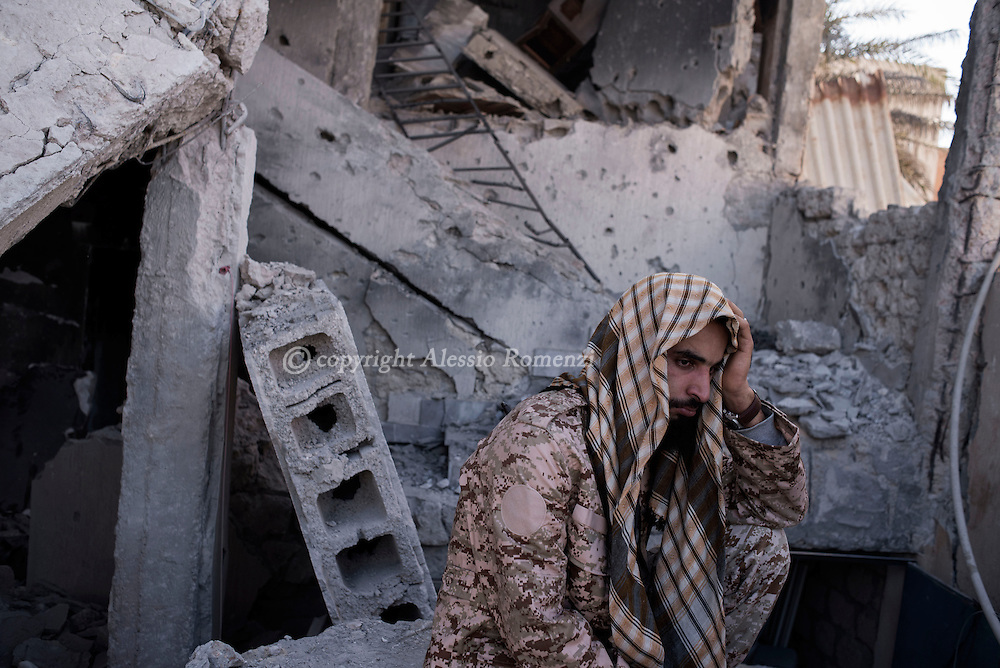 Libya, Sirte: After being informed of the death of one of his comrades, a fighter of the Libyan forces affiliated to the Tripoli government sits among the rubbles in Al Jiza neighbourhood on the frontline with ISIS in Sirte on November 24, 2016.  Alessio Romenzi