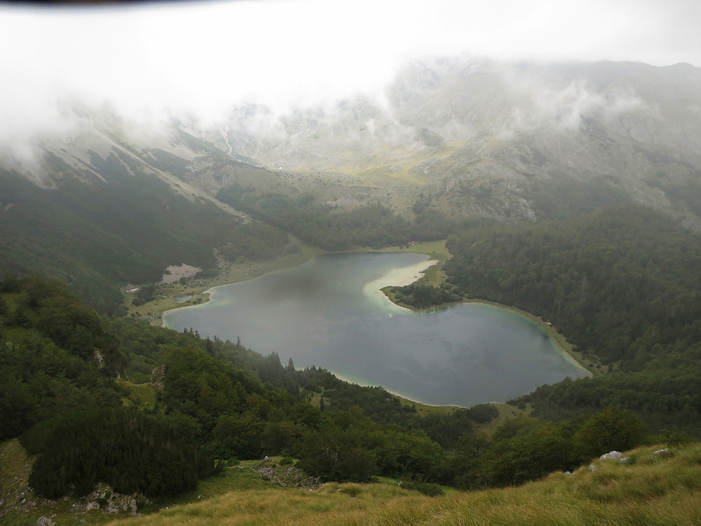 Mist rising over Trnovo Lake (Trnovacko jezero), to reveal the characteristic heart shape form of the lake.  Foot of Maglic and Volujak mountains, Bosnia and Herzegovina.