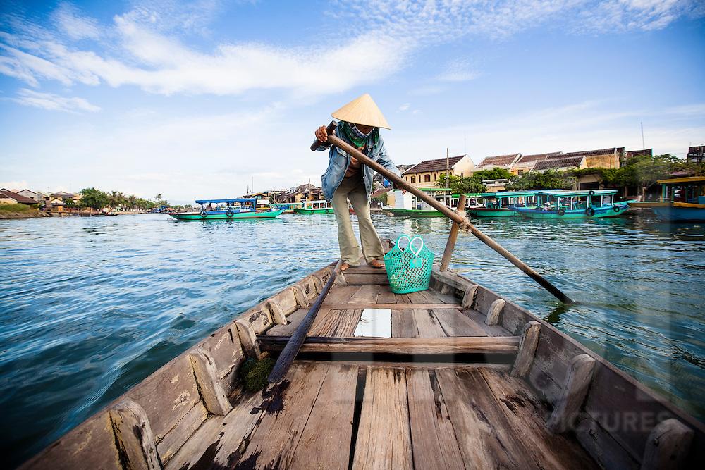 A Vietnamese woman rows a barge along Thu Bon River in Hoi An, Vietnam, Southeast Asia