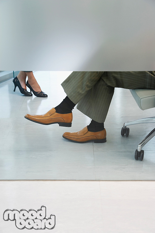 Office workers sitting in office low section (feet)