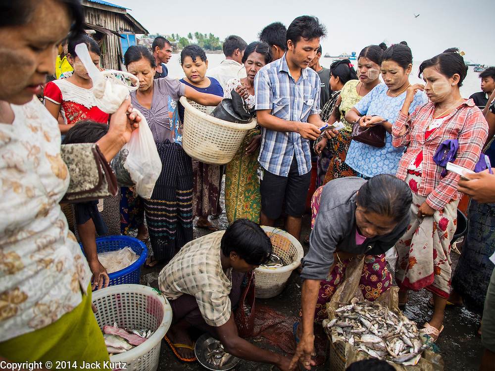 08 NOVEMBER 2014 - SITTWE, RAKHINE, MYANMAR:  A man auctions fresh fish brought into the pier in Sittwe. Fish are auctioned off as they are brought onto the pier. Sittwe is a small town in the Myanmar state of Rakhine, on the Bay of Bengal.  PHOTO BY JACK KURTZ