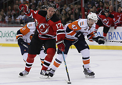Apr 10, 2010; Newark, NJ, USA; New Jersey Devils left wing Ilya Kovalchuk (17) and New York Islanders defenseman Andrew MacDonald (47) battle for the loose puck during the third period at the Prudential Center. The Devils defeated the Islanders 7-1.