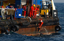 A diver of the Dutch salvage company SMIT prepares to climb on an oil recovery sea platform as it is towed to harbour from near the cruise liner Costa Concordia, which ran aground off the west coast of Italy, at Giglio island January 28, 2012. Salvage crews preparing to pump thousands of tonnes of diesel fuel and oil from the wreck of the Costa Concordia cruise ship off the Italian coast suspended work on Saturday because of bad weather that could last into next week, officials said.<br /> REUTERS/Darrin Zammit Lupi (ITALY)