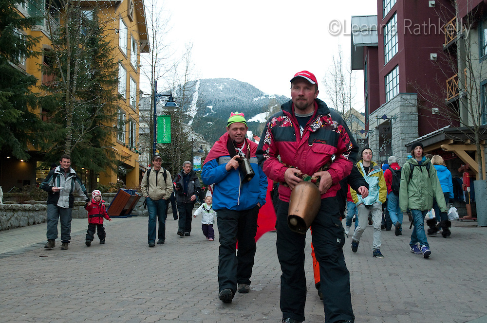 Swiss fans walk through Whistler Village ringing giant cowbells during the 2010 Olympic Winter games in Whistler, BC Canada.