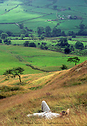 Man lying in long grass watching cloud shadows pass over the fields of Edale Valley, Peak District, England 2006